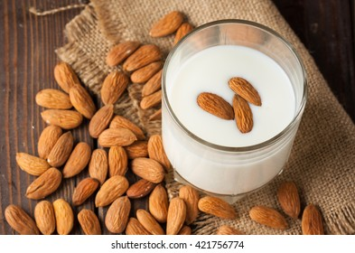 Almond milk in a glass with almond nuts on a wooden table. Healthy food concept.