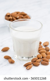 almond milk in a glass on table, closeup, vertical