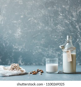 Almond milk in glass with almond pulp and almonds on wooden background with copy space.