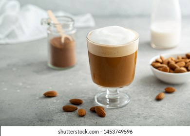 Almond milk latte with thick foam in a glass