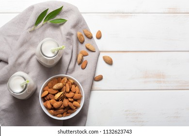 Almond milk on a white wooden table. Top view with copy space