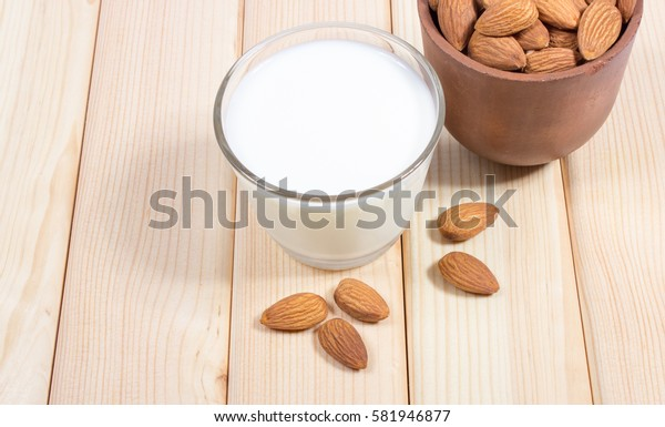 Almond milk with almond on a wooden table - vegan drink.