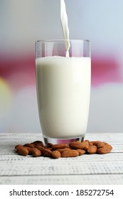 Almond milk is poured into glass, on color wooden table, on light background