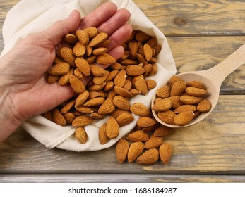 Almond nut in the hand of a woman. Wooden spoon with almonds. Healthy diet. Space for text. Agriculture. Agricultural industry. On a vintage wooden background. Close up.