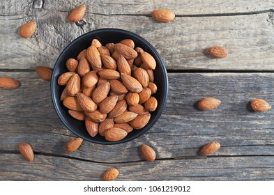 Almond nuts in black bowl and scattered on old wooden table. Selective focus