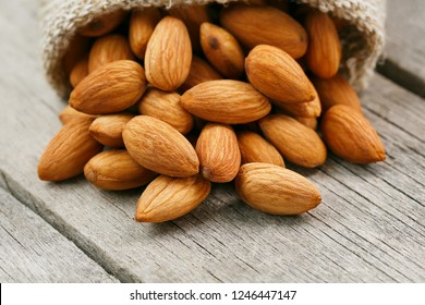 Almond nuts in a burlap bag on a wooden gray background.
