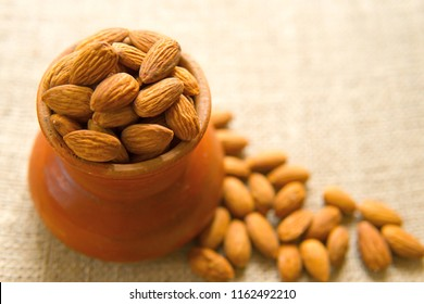 Almond nuts in earthenware on sackcloth background, almonds are unsaturated fats food benefit for decrease blood cholesterol level and good nutrition during diet and lost weight,selective focus