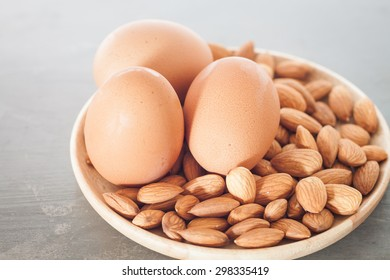 Almond nuts and eggs on wooden plate, stock photo