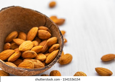 Almond nuts in half coconut shell on white wooden background, side view from above, close-up