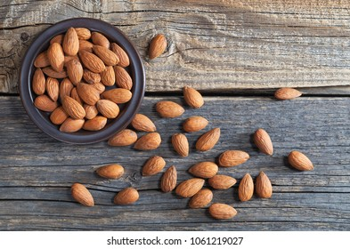 Almond nuts in plate and scattered on old wooden table, top view. Healthy food