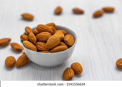 Almond nuts in a white glass bowl on a white wooden background, side view from above, close-up