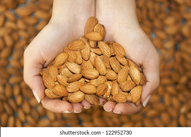 Almond nuts in the woman's hands forming heart shape