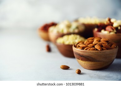 Almond nuts in wooden bowl. Food mix background, top view, copy space, banner. Assortment of nuts - cashew, hazelnuts, almonds, walnuts, pistachio, pecans, pine nuts, peanut, raisins.
