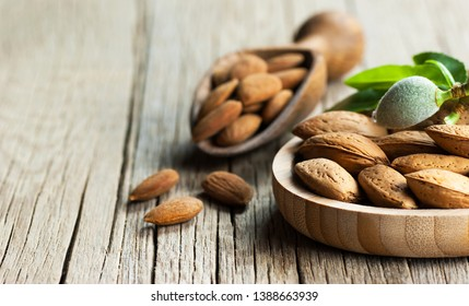 Almond nuts in wooden shovel, almonds with shell in bamboo bowl on wooden background with green fresh raw almonds on almond tree branch