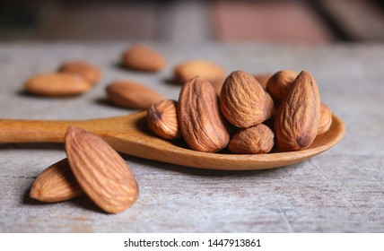 Almond nuts in wooden spoon on rustic background. Almonds are healthiest nuts and one of the best brain foods.