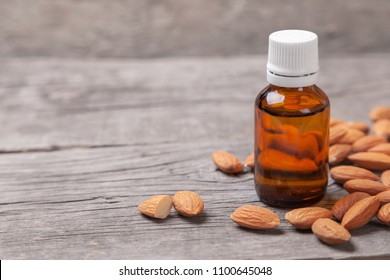 Almond oil in a bottle on wooden table. Copy space for text