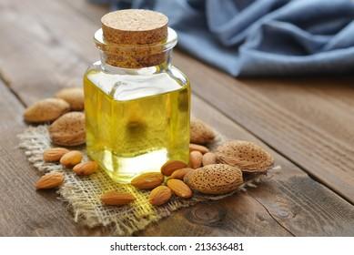 Almond oil in bottle on wooden background