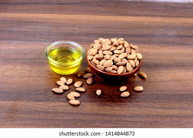 Almond oil and bowl of almonds on wooden background Top view - Image