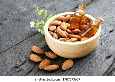 Almond oil in a clear glass bottle, placed in a brown wooden cup filled with roasted almond seeds and poured on a black wooden floor.