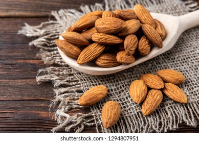 Almond on wooden spoon on wooden background.