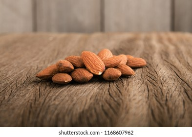 Almond pile multi vitamin on wood background in vintage tone