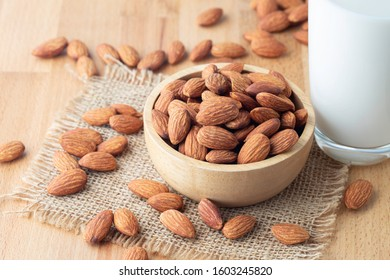 Almond seeds in a bowl wood on the sackcloth And a glass of milk on table wooden background