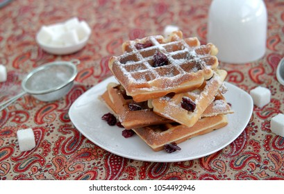 Almond waffles with dried cranberries sprinkled with powdered sugar