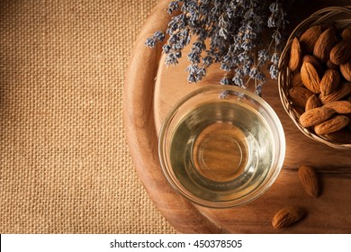 Almonds and almond oil on wooden background. Skin and hair care concept. Lavender and nuts.