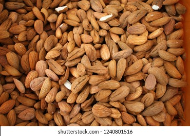 Almonds. Background of big raw peeled almonds situated arbitrarily. Nuts wallpaper pattern. Clipping path. Peeled almonds close up. For vegetarians. Nut pattern.