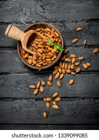 Almonds in bowl with wooden scoop. On black rustic background.