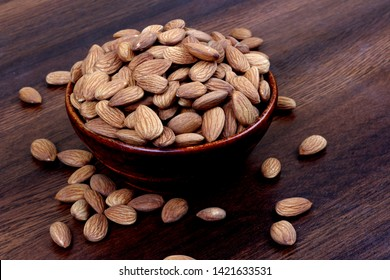 Almonds in brown bowl on wooden background – Image