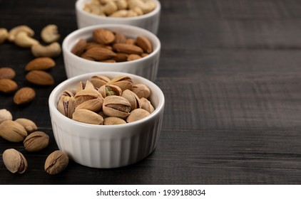 Almonds with cashews and pistachios in white ceramic cups on a dark wooden background. Copy space, no people, flatlay, close-up