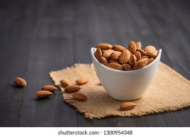 Almonds in ceramic bowl on dark wood table. Almond concept with copyspace.