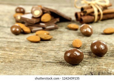 Almonds in chocolate glaze on a old wooden table. Unhealthy food. Risk of obesity and diabetes. Sweet nuts. Almond chocolate dragees.