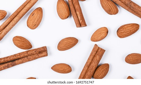 Almonds and cinnamon sticks on a white background. Flat lay. Food pattern.