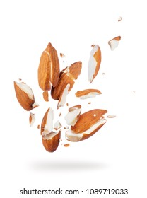 Almonds crushed into pieces, frozen in the air close-up on a white background