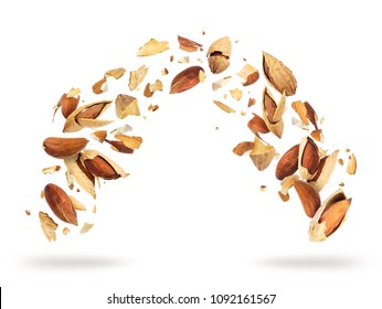 Almonds crushed into pieces, frozen in the air on a white background