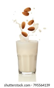 Almonds falling into almond milk. A glass of almond milk on a white surface.