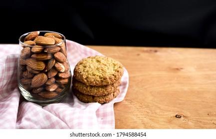 Almonds in the glass with oatmeal cookies on the wooden table. Zero sugar cookies. Sugar free. Zero calorie. Healthy food snack concept.