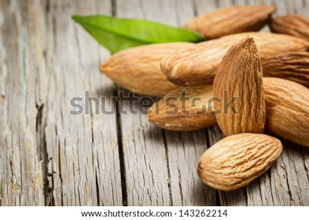 Almonds with leaf on wooden background