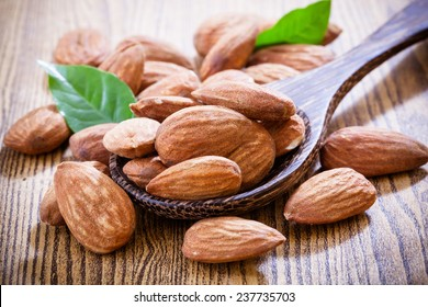 Almonds with leaves isolated on wood background