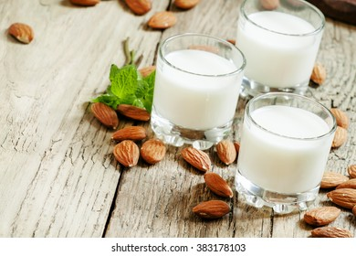 Almonds and milk, old wooden background, rustic style, selective focus