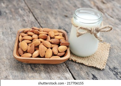 almonds milk  with almonds on dish.