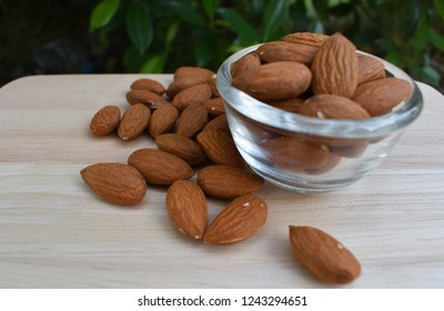 Almonds, multi-grain almonds, wooden table almonds, clear almonds in a glass bowl.