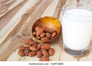 Almonds nuts and almond milk on wooden table