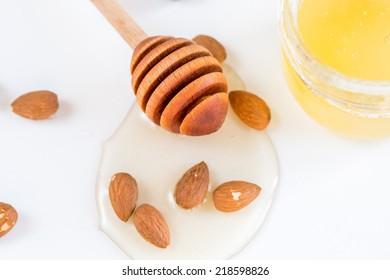 Almonds nuts with honey on white. Component in cookery