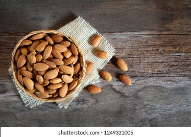 Almonds nuts in wooden bowl on wood table,Top view.