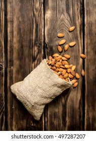 The almonds in an old bag. On a wooden table.