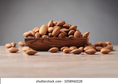 Almonds in old wooden dish on a kitchen table, copy space.