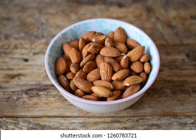 Almonds on a plate. Wooden background